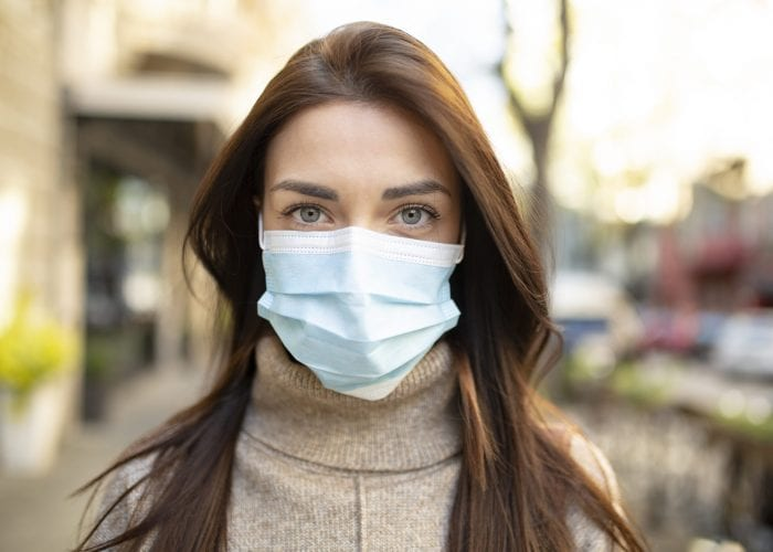 Portrait of an attractive young woman wearing a face mask to protect herself and others from airborne viruses while being outdoors in the city