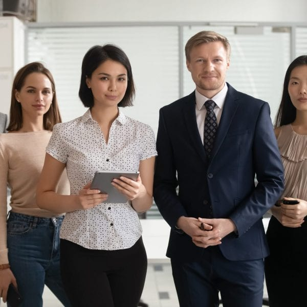 Portrait of happy smiling diverse employees team standing in office, holding phone and tablet, posing for company photo together, looking at camera, workers group motivated for business success